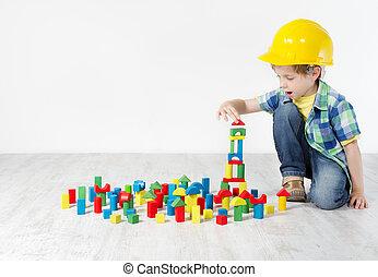 Chico con sombrero duro jugando con bloques: la ciudad de construcción. El concepto de desarrollo y construcción