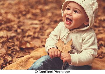 Chico feliz en el bosque de otoño