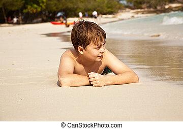 Chico feliz tirado en la playa
