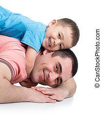 Chico feliz y su padre tirados en el suelo