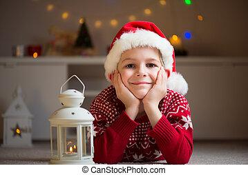 Chico guapo feliz tirado en el suelo con sombrero rojo y esperar Santa Claus
