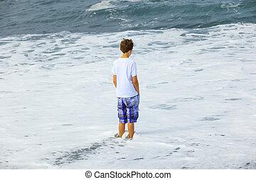 Chico mirando las olas del océano