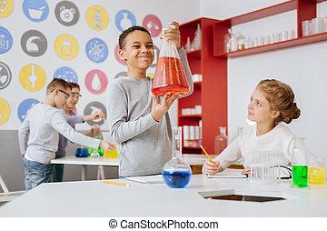 Chico optimista mirando frascos con químicos rojos