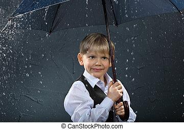 Chico sonriente vestido de camisa blanca y chaleco negro bajo el paraguas bajo la lluvia