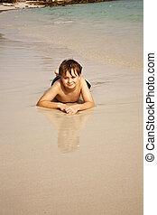 Chico tirado en la playa y disfrutando de la calidez del agua y luciendo seguro y feliz