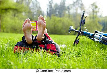 ciclista, descalzo, alto, lee, verde, fresco, pasto o césped, acostado