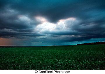 Cielo oscuro con nubes de lluvia sobre el campo verde, clima tormentoso