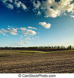 Cielo oscuro con nubes sobre el campo arado