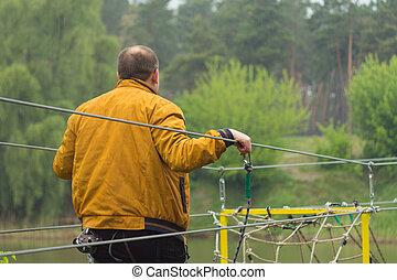 Cierra al hombre cruzando el río en el puente de la cuerda