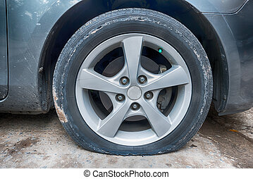 Cierra la rueda pinchada de un coche viejo y sucio