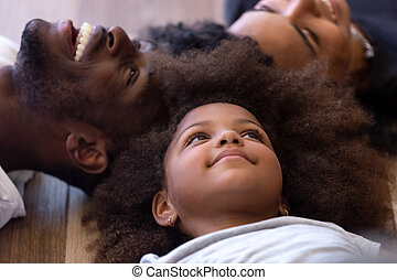 Cierren la feliz familia afroamericana acostada en suelo caliente juntos