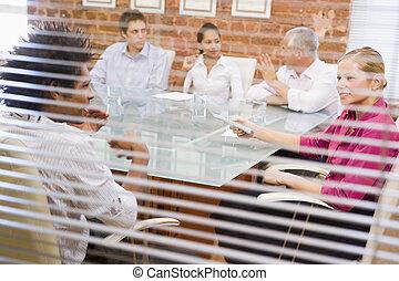 Cinco hombres de negocios en la sala de juntas por la ventana