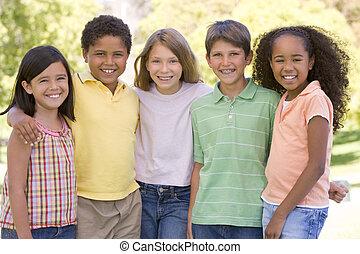 Cinco jóvenes amigos al aire libre sonriendo