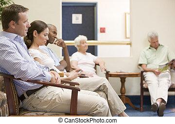 Cinco personas esperando en la sala de espera
