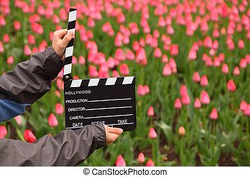 Cine clapper en manos de chico en el campo con tulipanes