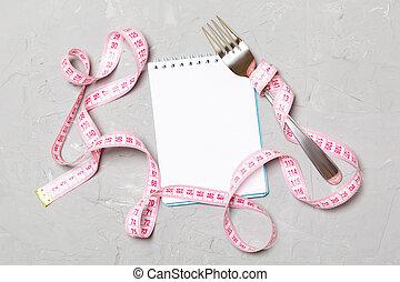 Cinta rosada, libreta abierta y tenedor en fondo de cemento con espacio vacío para tu idea. La mejor vista del concepto de estilo de vida saludable