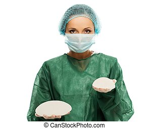 Cirujana plástica con gorra y máscara sosteniendo implantes de silicona