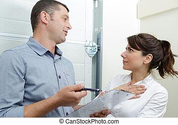 Cliente femenina hablando de contrato con fontaneros dentro