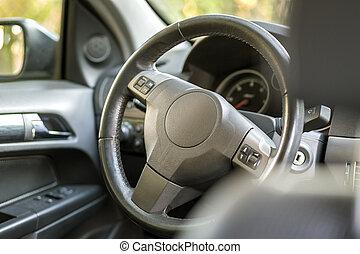 Coche moderno y caro interior de lujo negro. Rueda de dirección, tablero, parabrisas y espejo. Transporte, diseño, concepto de tecnología moderna.
