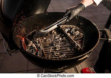 cocinero, close-up., guantes, parrilla, negro, utilizar, tenazas, transferencias, carbones, macho, neatly