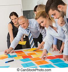 Colegas de negocios arreglando etiquetas en la mesa