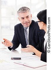 Colegas de negocios en el trabajo. Dos alegres empresarios discutiendo algo y gesticulando mientras sentados juntos en la mesa