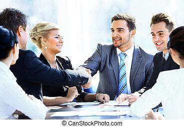 Colegas de negocios sentados en una mesa durante una reunión con dos ejecutivos dándose la mano
