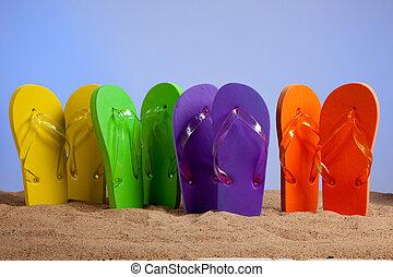 Coloridas sandalias en una playa de arena