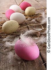 Coloridos huevos del este con plumas en la mesa vieja
