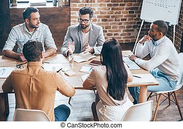 Combinando su experiencia. La mejor vista de los jóvenes empresarios discutiendo algo mientras están sentados juntos en la oficina