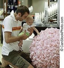Compras familiares. El joven padre y su hija en el centro comercial. Muestra un enorme ramo floral