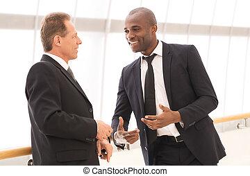 Comunicación de negocios. Dos alegres hombres de negocios hablando entre sí y gestando