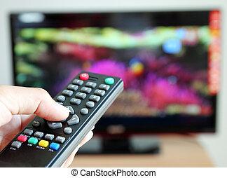 Con la mano apuntando un control remoto de TV hacia la televisión
