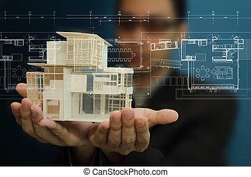 Con un modelo de casa en sus manos.