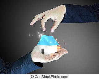 Concepte la imagen de una casa que sostiene la mano