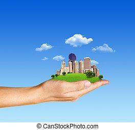 Concepto la mano humana sosteniendo una ciudad sobre hierba verde