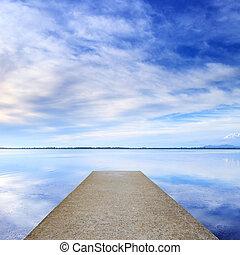 Concrete pier o jetty y en un lago azul y el cielo se refleja en el agua.