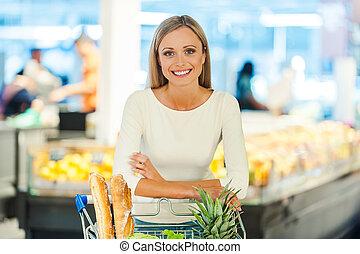 Confiado en su elección de comida. Una joven sonriente apoyada en el carrito de la compra y mirando a la cámara mientras estaba parada en una tienda de alimentos