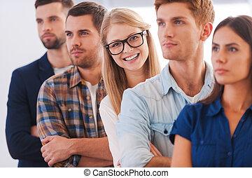 Confiado en su equipo. Una joven atractiva sonriendo mientras está en fila con otras personas
