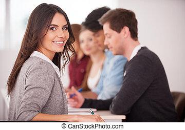 Confiado en su equipo. Vista trasera de una hermosa joven mirando por encima del hombro y sonriendo mientras sentados juntos en la mesa con otra gente