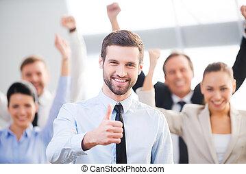 confiado, sentimiento, hombre de negocios, arriba, feliz, plano de fondo, pulgar, team., actuación, prestigio risueño, el suyo, colegas, mientras