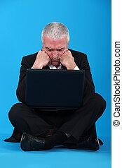Confundido hombre de negocios de mediana edad con portátil