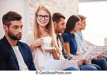 ¡Conseguiré este trabajo! Un grupo de jóvenes con ropa informal elegante sentados en una fila en las sillas y sosteniendo papeles mientras una mujer hermosa bebe café y sonríe