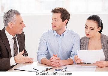 Consulta financiera. Una pareja joven sentada junto a la mesa mientras el hombre de trajes de gala le dice algo y gesticula