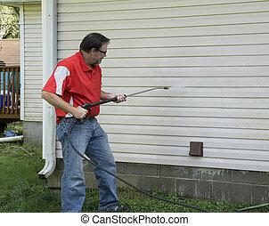 Contractor usando una lavadora de presión para limpiar revestimiento de vinilo