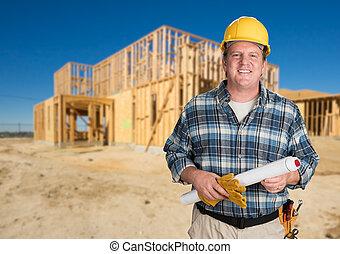 Contratista con planes y sombrero duro frente a una nueva casa enmarcada en la construcción.