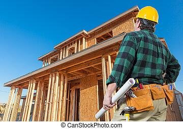 Contratista frente a una nueva casa enmarcada en construcción