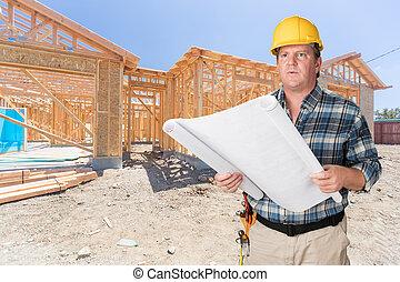 Contratista masculino con planes de casa usando sombrero duro delante de la construcción de casas nuevas