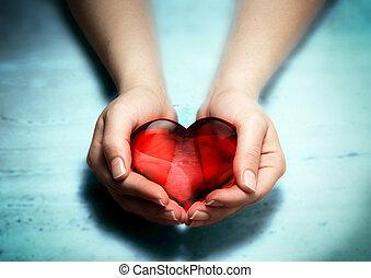 Corazón de cristal rojo en manos de mujer