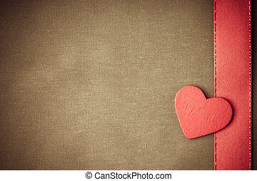 Corazón decorativo de madera roja sobre fondo de tela beige.